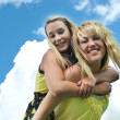 Girl Friends Piggyback Ride in Sunshine — Stock Photo #4637626