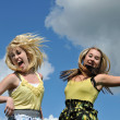 Two girls jumping in the sky — Stock Photo