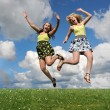 Two girls jumping over grass hill — Stock Photo