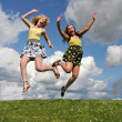 Two girls jumping in grass field — Stock Photo