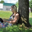 Girl reading book under tree in shade — Stock Photo