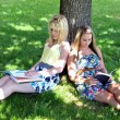 Girls reading books under tree in shade — Stock Photo