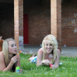 Two Girl Friends Blowing Bubbles in Grass — Stock Photo #4637794