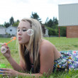 Girl Blowing Bubbles in Grass — Stock Photo #4637802