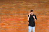 Student standing in front of brick wall — Stock Photo