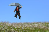 Businessman Jumping over Grass Hill — Stock Photo