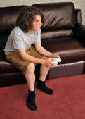 Single boy playing video games on couch — Stock Photo