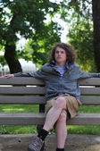 Teenager sits on bench and relaxes while thinking — Stock Photo