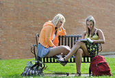 Teenage girls sitting in front of school — Stock Photo