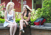 Teenage girls talking in front of school — Stock Photo