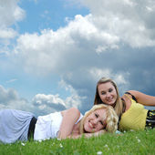 Two girl friends laying in grass — Stock Photo