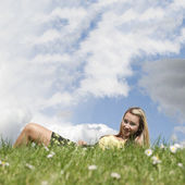 Girl laying on grass hill with copyspace sky — Stock Photo