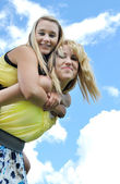 Piggyback ride with two teenage girls — Stock fotografie