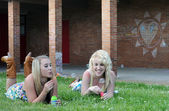 Two Girl Friends Blowing Bubbles in Grass — Stock Photo