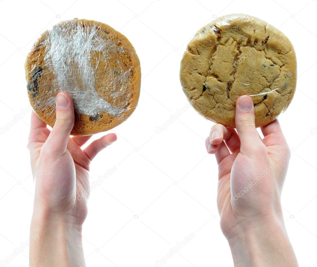 Two hands holding two cookies that are packaged n shrink plastic wrap isolated on a white background — Stock Photo #4630204