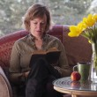 Stock Photo: Female reading book by table with daffodils