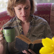 Baby boomer Mum taking a break and reading a book — Stock Photo