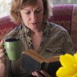 Stock Photo: Baby boomer Mum taking break and reading book