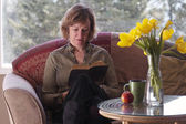 Female reading book by table with daffodils — Stock Photo
