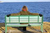 Solitaria donna seduta sulla panchina in primavera — Foto Stock
