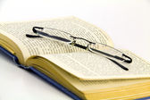 Close up of antique book with reading specs — Stock Photo