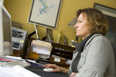 Woman working at home computer — Stock Photo