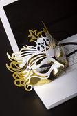 Mardi Gras mask on a white laptop. — Stock Photo