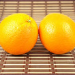 Fresh orange on bamboo table cloth — Stock Photo
