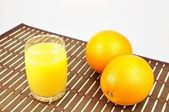 Fresh orange and juice on table cloth — Stock Photo