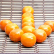 Mandarin baby orange made an arrow sign — Stock Photo