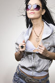 The glamour Latin girl in dark glasses undressing a jacket — Stock Photo
