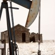 Pump jack near abandoned homestead - Stock Photo