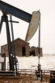Pump jack near abandoned homestead — Stock Photo