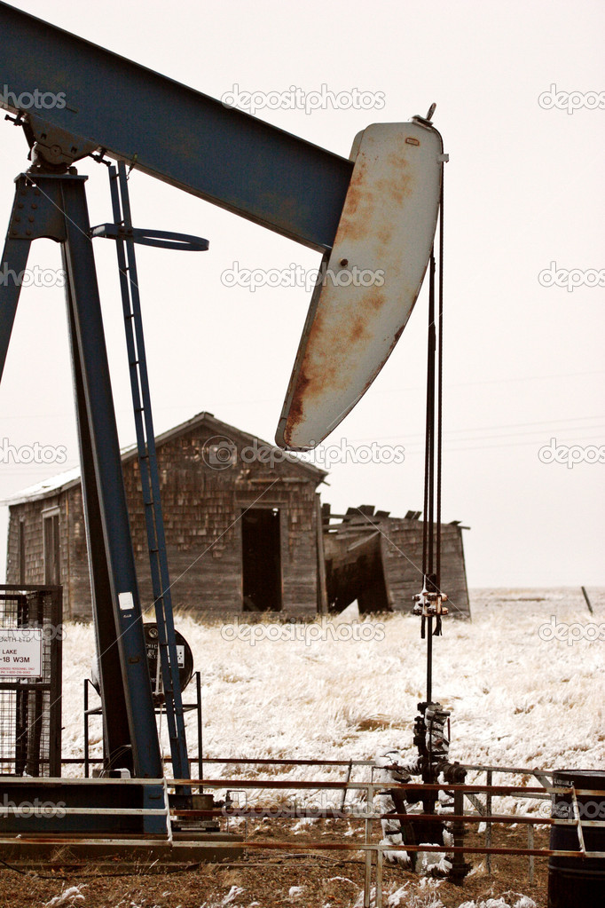 Pump jack near abandoned homestead — Stock Photo #4845703
