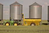 Farm machinery left by grain vaults — Stock Photo