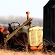 Abandoned tractor by old granaries — Stock Photo