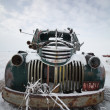 Frontend of an abandoned olf farm truck in winter - Stock Photo