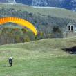 Stock Photo: Paraglider landing in field near chapel