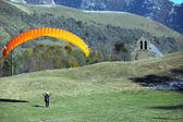 Paraglider landing in a field near a chapel — Stock Photo