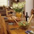 Dining table set with salad bread and wine - Stock Photo