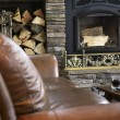 Leather sofa and unlit fireplace - Stock Photo