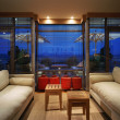 Lights on in living room, view of city skyline through window, night - Stock Photo