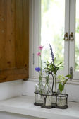 Jars of flowers on window sill — Stock Photo