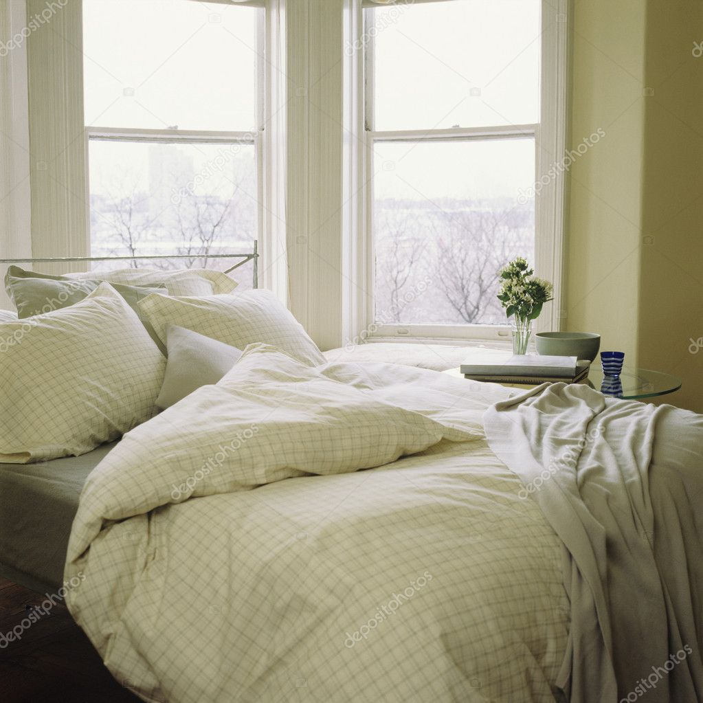 Bed with linens, comforter beside window — Stock Photo #4908669