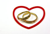 Gold rings in red heart shape — Stock Photo