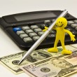 Paper money, pen, calculator and action figure — Stock Photo
