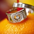 Stock Photo: Wedding rings on orange