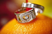 Wedding rings on an orange — Stock Photo