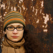 Beautiful young adult woman in a cap and glasses against a grungy rusty w — Stock Photo #4929102