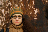 Beautiful young adult woman in a cap and glasses against a grungy rusty w — Stock Photo